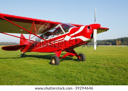Small lightweight private airplane standing on airfield grass
