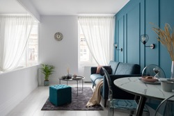 Small living room with glass wall, molding on teal blue wall and elegant furniture