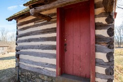 Small log cabin exterior with a red wooden door. Colonial Pennsylvania construction with nature background.