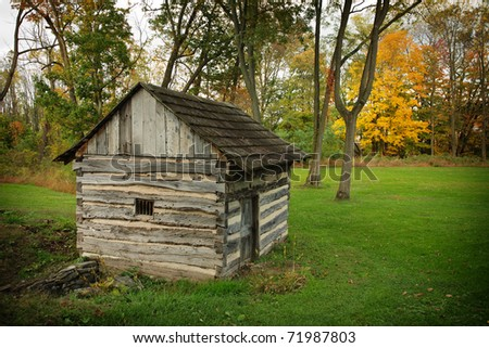 Small log spring house in autumn