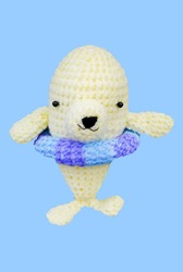 Small lovely white dophin toy in crochet handmade on blue background and clipping path .
