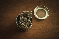 Small magnetic balls in a round box, a puzzle toy.