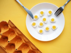 small marmalade scrambled eggs on a white plate and egg packaging. yellow background