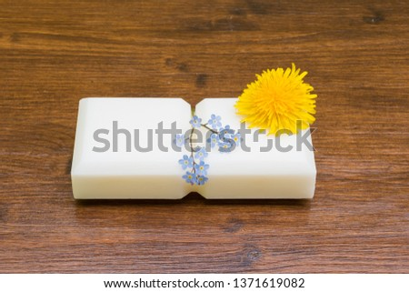 Small marseille soap isolated with flowers on wooden table in the foreground.foreground. #1371619082