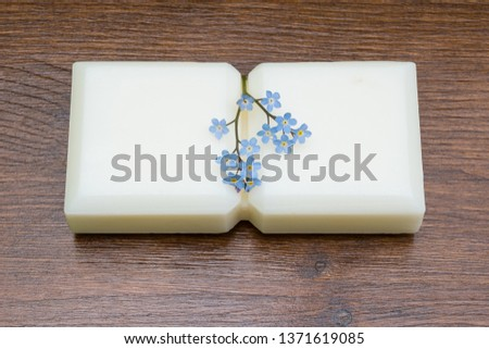 Small marseille soap isolated with flowers on wooden table in the foreground.foreground. #1371619085