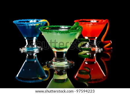 small martini glasses poured and garnished with sugar rims all different colors