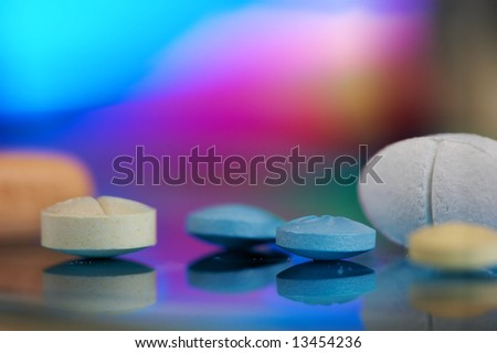 Small medicine tablets against a rainbow coloured background - stock photo