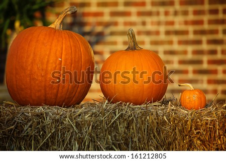 Small, Medium, and Large size pumpkins on top of a hay bale during as part of a Halloween decoration.