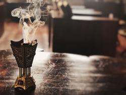 Small metal decorative Arabian Bakhoor incense burner censer with smoke and blurred background.