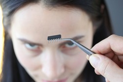 Small microcircuit chip in front of woman's head. Human microchip implant concept