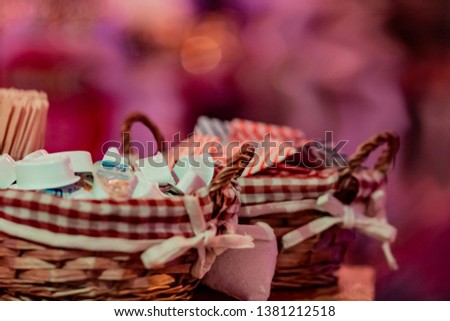 Small milk, coffee creamer pots in basket on red blur background. Mono portions, for catering