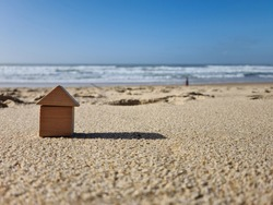 Small miniature kids wooden toy home model on sunny sand beach with blue sky and white clouds and ocean background. Copy space of family lifestyle and business real estate property investment concept