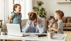 Small mischievous kids noising and distracting mother freelancer trying to concentrate on laptop and squeezing head working at table in light living room