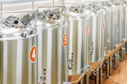 Small modern brewery, production. Rows of steel tanks for beer fermentation and maturation. Equipment for staged production bottling of Finished food products. Metal structures at enterprise factory.