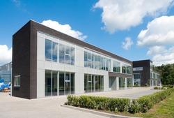 small modern office building against a nice cloudy sky