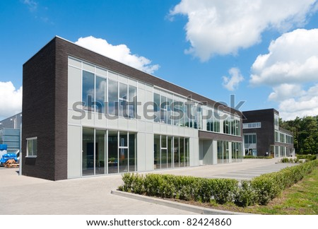 small modern office building against a nice cloudy sky