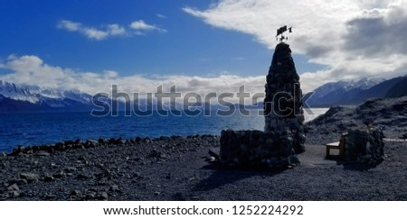 Small monument and a place to sit on a rocky beach in the Alaskan mountains.  #1252224292