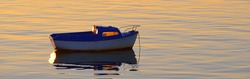Small motor boat anchored in Lilia bay near the Île Vierge lighthouse at sunset. Plouguerneau, Finistère, Brittany, France. Clear pink sky, reflections on the water. Travel, recreation. Panoramic view