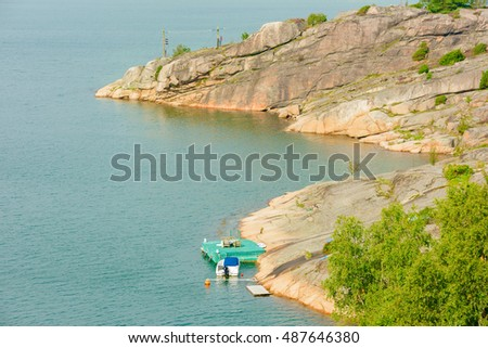 Stock Photo Small motorboat moored at green wooden pier in Swedish west coast landscape.