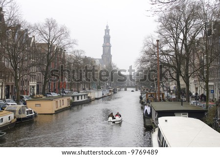 small motorboat on famous canal in Amsterdam with Westertoren in background