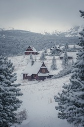 Small mountain village in winter, Tatras National Park, Poland. Old wooden huts in snow. Traditional architecture of Podhale region. Selective focus on building exterior, blurred background.