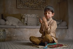 Small muslim boy in prayer cap and arabic clothes with rosary beads and holy Koran book praying to Allah, ramadan kareem concept young kid spiritual peaceful moment inside eastern traditional interior