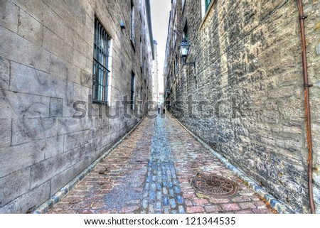 Small narrow street in Old Montreal, and in the background a man walking with his dog, HDR image