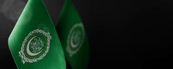 Small national flags of the Arab League on a dark background