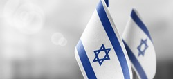 Small national flags of the Israel on a light blurry background