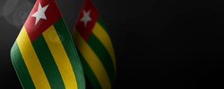 Small national flags of the Togo on a dark background