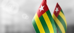 Small national flags of the Togo on a light blurry background