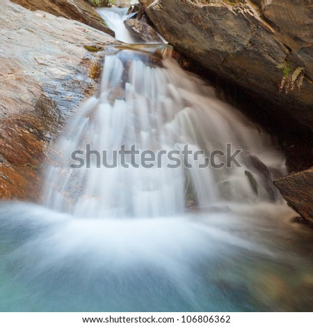 Small natural waterfall casdcading over rocks into a calm blue pond below with silky appearance from long exposure