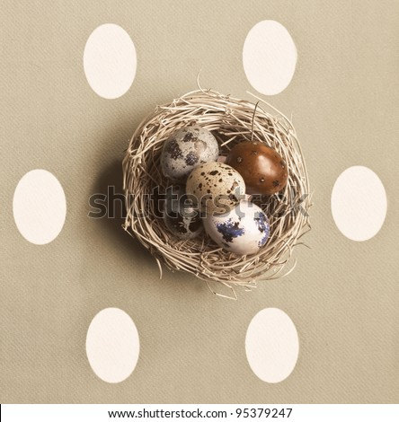Small nest containing colored eggs over a Easter concept background