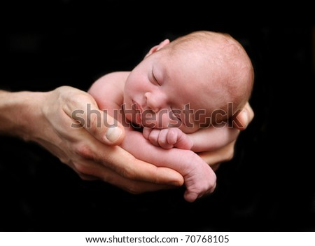 Small newborn baby being held in her dad's hands