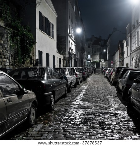 Small night street with car parking on Montmartre, Paris.