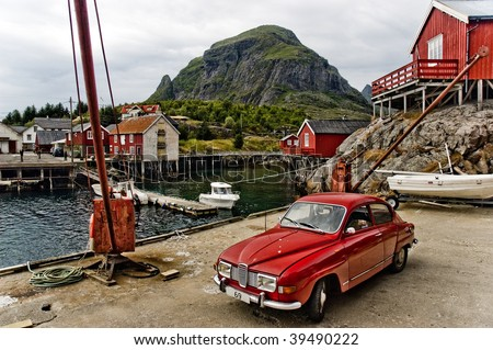 Small Norwegian fishing village - red houses, old car, small port with crane. all under majestick mountain. Lofoten islands.