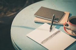 Small notebook and pen beside coffee cup on blue color round wood table at outdoor area in cafe with morning scene and vintage filter effect