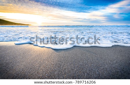 Small ocean sea waves on sandy beach with sunrise sunset. Background landscape picture of dusk or dawn at the Atlantic ocean beach with small waves at low tide. Background wallpaper picture.