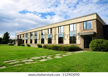 Small office or business building or college school perspective shot with sky and grass.