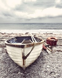 Small old fishing boat on a Cornish beach with instagram style filter