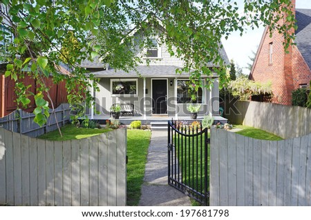 Small old house. Front fenced yard with open gate. View of walkway and entrance porch