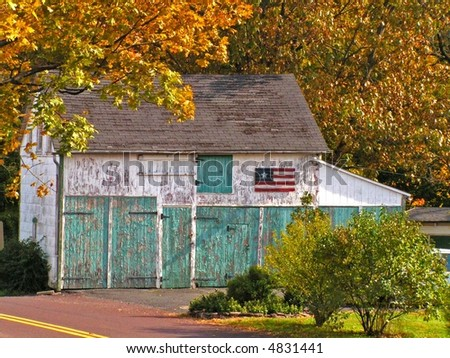 Small old white barn with aqua doors and peeling paint.  A folk style American Flag adorns the side of the barn.  Beautiful autumn setting.