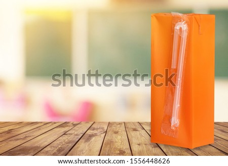 small orange drinks carton with straw