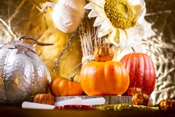 Small orange pumpkins, small red pumpkin, small orange glitter pumpkins, a large silver pumpkin, red, yellow, and orange glitter leaves, and dried sunflowers against a golden background