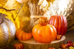 Small orange pumpkins, small red pumpkin, small orange glitter pumpkins, yellow, red, and orange glitter leaves, silver pumpkin, and dried sunflowers against a golden background