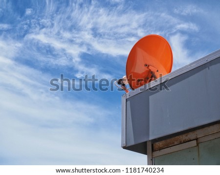 Small orange satellite dish mounted on the roof of the house for receive signals from space to amplify the signal to watch television and blue sky with white pattern clouds. #1181740234