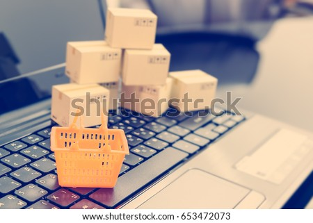 Small orange shopping basket on a laptop keyboard with boxes behind. Concept of shopping that consumers or customers can buy products or services online directly from sellers on the internet worldwide #653472073