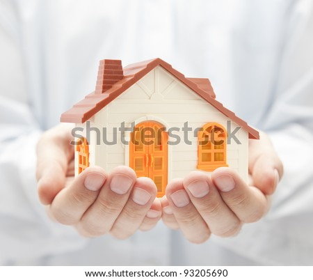 Small orange toy house in hands