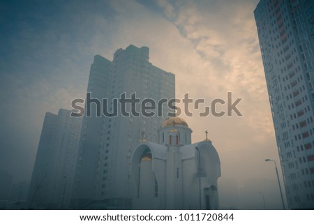 Small orthodox church at modern city residential district among high multi-storey buildings. Frosty foggy morning at city street. Kiev. Ukraine.