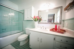 Small outdated tile bathroom with a clear glass door and a white cabinet sink vanity and mirror